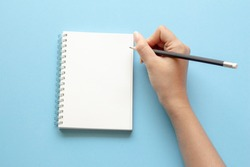 woman's hands writing in empty notebook at the blue desk. Flat lay top view.