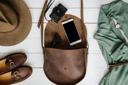 Woman's journalist or traveler accessories on white wooden table background flat lay. Brown leather purse, marine shoes, mobile cellphone, belt, watch, retro film camera. Empty space for copy, text.
