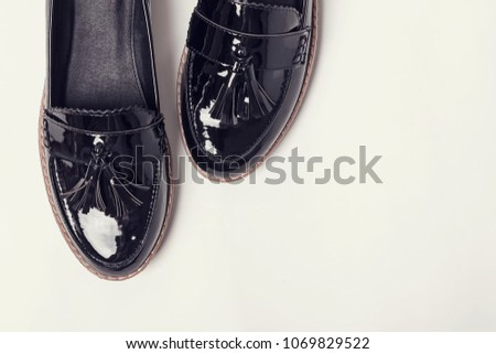 Woman's lacquered loafer shoes on the white background, top view, toned photo.