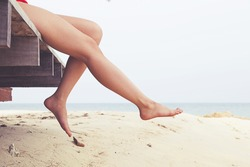 Woman's legs at beach jetty