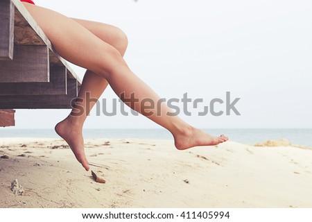 Woman\'s legs at beach jetty