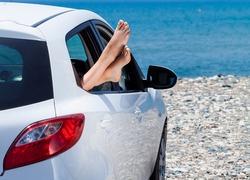 Woman's legs dangling out a car window