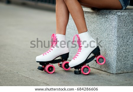 Woman's legs in a vintage roller skates.  white quad roller skates. Outdoor.