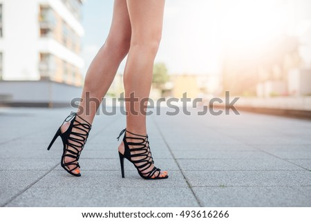 Woman's legs in high heels. Urban background. #493616266