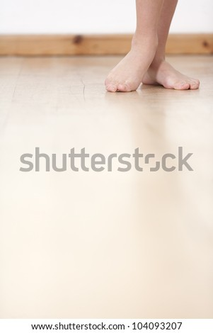 Woman's legs on wooden floor against a white wall back drop.