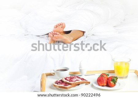 woman's legs under the blanket and breakfast near the bed