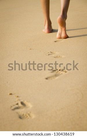 Woman's legs walking in the sand