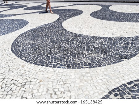Woman's legs walking through the promenade from the famous Copacabana beach - side of the bike path - paved road with stones - Rio de Janeiro - Brazil