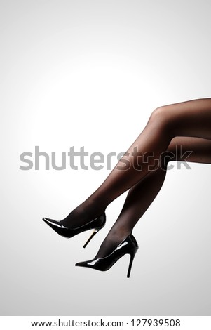 Woman's Legs Wearing Pantyhose and High Heels Isolated Against a White Studio Background