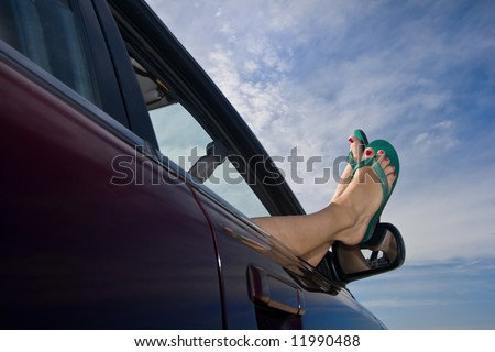 Woman's legs with bright green flip-flops (sandals) dangling out a car window parked at the beach