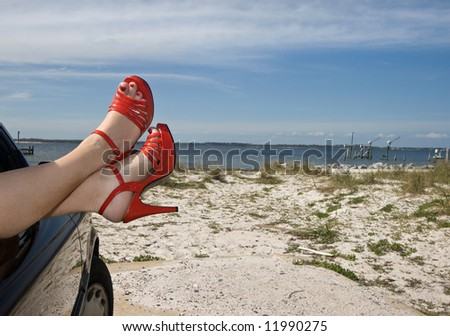Woman's legs with red patent leather spike heels dangling out the car window parked at the beach