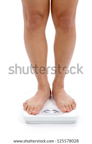 Woman's lower legs and feet shown on a bathroom scale for weight loss concept.