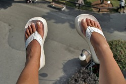 Woman's manicured feet dangling from a carnival ride up above the park