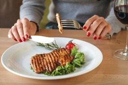 Woman's manicured hand holding fork with grilled chicken steak. Grilled chicken breat with salad, cherry tomato and rosemary on a plate in a restaurant. Concept of eating out.