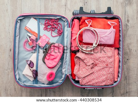 Woman's open bag on a desktop with clothing and accessories, she is packing and getting ready to leave, travel and vacations concept
