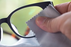 Woman's right hand cleaning grey shortsighted or nearsighted eyeglasses by grey microfibre cleaning cloths, Bokeh green background, Close up & Macro shot, Selective focus, Optical concept