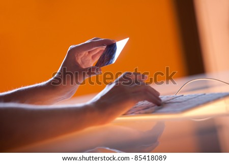 Woman's right hand holding a credit card above a keyboard getting ready to enter data