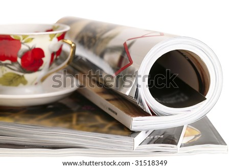 Woman's rolled glossy magazine in stack with tea cup. isolated with clipping path