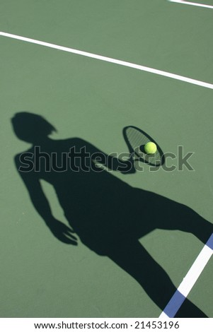 Woman's shadow holding racket with tennis ball on court