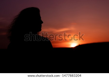 Woman's silhouette on the beautiful sunset, dreamy concept #1477883204