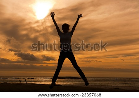woman's silhouette with her hands raised in the sunset