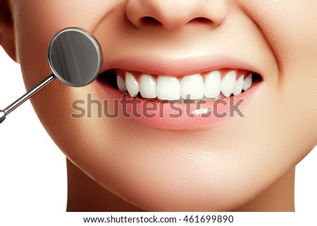 Woman\'s smile. Healthy white woman\'s teeth and a dentist mouth mirror closeup. Dental hygiene, oral care concept. Examination at dentistry with dental tools. Teeth whitening. Stomatology concept