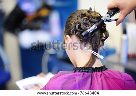 Woman's stylist's hands making a fancy hairstyle