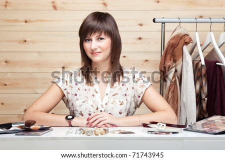 Woman's stylist with attributes of her work, standing near coat rack with clothes. Cosmetics and accessories on the table in front of her.