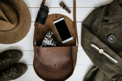 Woman's traveler apparel and  accessories on white wooden background flat lay. Brown leather purse, hiking boots, jawharp, contemporary mobile cellphone, military jacket, watch, film camera, compass.