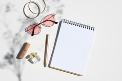 Woman's workplace concept mockup. Feminine accessories with spiral notepad and flower branch shadow. Top view trendy shadows mockup with copy space