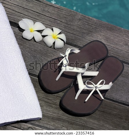 woman sandals and towel on the wooden flipflop near the water