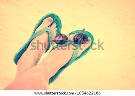 f9470ceb92493 Woman sandy bare feet with flip flops and sunglasses