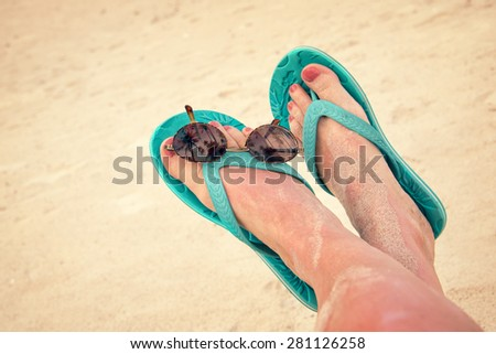 Woman sandy bare feet with flip flops and sunglasses, vintage process #281126258