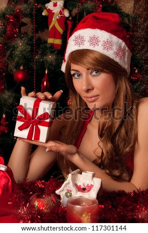 Woman santa helper with present under Christmas tree