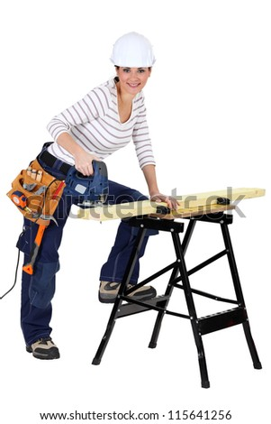 Woman sawing wood with electrical saw