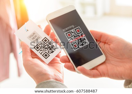 Woman scanning QR code from a label in a shop with mobile phone #607588487