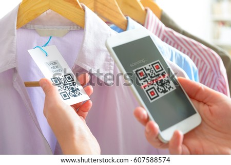 Woman scanning QR code from a label in a shop with mobile phone #607588574