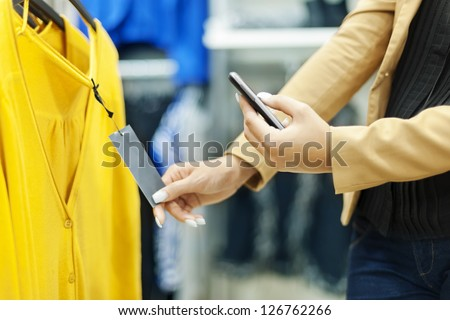 Woman scanning QR code in shopping mall