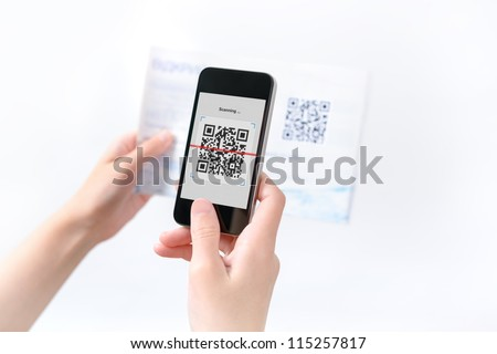 Woman scanning QR code in the magazine on mobile smart phone.