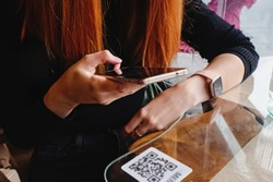 Woman scanning the barcode qr code in restaurant or cafe