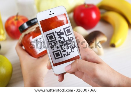 Woman scanning voucher code with mobile phone close up
