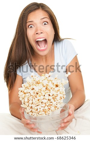 Woman scared funny watching scary movie. Beautiful girl watching movie in bed on white background