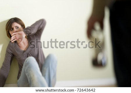 Woman scared of a man holding a bottle; Concept: abuse/domestic violence due to alcoholism