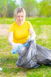 Woman scavenges garbage in the summer park. Volunteer and ecology concept
