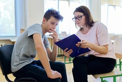 Woman school psychologist talking and helping student, male teenager. Mental health of adolescents, psychology, social issues, professional help of counselor