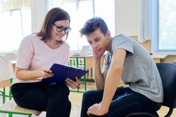 Woman school psychologist talking and helping student, teenage boy. Mental health of adolescents, psychology, social issues, professional help of counselor