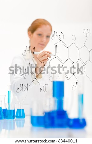 Woman scientist in laboratory write chemical formula with test tube and beaker