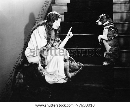 Woman scolding dog on stairs
