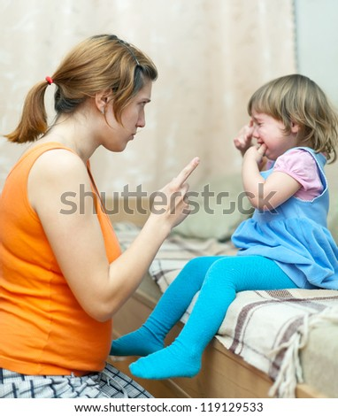 Woman scolds crying child at home. Focus on woman