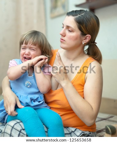 Woman scolds crying child in home interior. Focus on woman #125653658